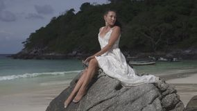 Beautiful girl on tropical island. Beautiful brunette woman in white dress relaxing on the rock on the tropical paradise island beach - video in slow motion stock footage