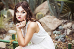 Beautiful brunette woman in white dress and sensual pose in cactus garden Royalty Free Stock Images
