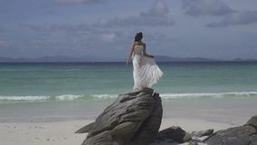 Beautiful girl on tropical island. Beautiful brunette woman in white dress standing on the rock on the tropical paradise island beach over blue sky and sea stock footage