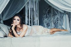 Beautiful Brunette Woman in White Lingerie Lying. In Bed and Posing in Boudoir Room Royalty Free Stock Image