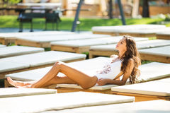 Beautiful brunette woman in a white swimsuit near the pool. A woman is sunning on a white chaise longue. Royalty Free Stock Photo