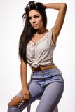 Beautiful brunette woman in white top and jeans on chair Stock Photos
