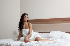 Beautiful brunette woman in white towel on bed Stock Photos