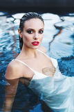 Beautiful brunette woman in white wet dress lies in the water. Woman in the pool. Beautiful brunette woman in white wet dress lies in the water Royalty Free Stock Images