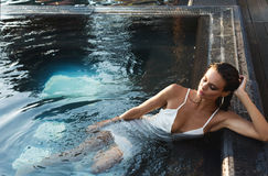 Beautiful brunette woman in white wet dress lies in the water. Woman in the pool.  Stock Images