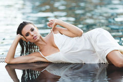 Beautiful brunette woman in white wet dress lies in the water. Woman in the pool.  Royalty Free Stock Photo