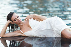 Beautiful brunette woman in white wet dress lies in the water. Woman in the pool Royalty Free Stock Images
