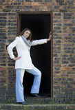 Beautiful brunette woman in white winter coat and jeans, posing in barn doorway Royalty Free Stock Photo
