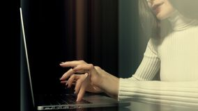 Beautiful brunette woman working on her laptop against black background. Abstract light vertical lines across the frame Royalty Free Stock Photos