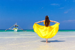 Beautiful brunette woman in yellow dress with her back to the vi Stock Photos