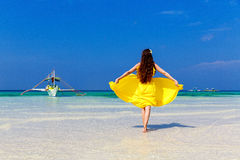 Beautiful brunette woman in yellow dress with her back to the vi Stock Images