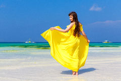 Beautiful brunette woman in yellow dress with her back to the vi Royalty Free Stock Photo