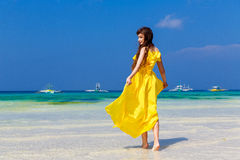 Beautiful brunette woman in yellow dress with her back to the vi Stock Image