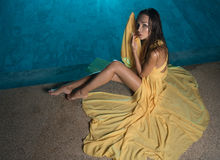 Beautiful brunette woman in yellow dress by the pool Royalty Free Stock Photography
