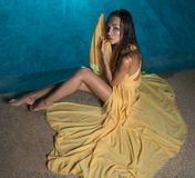 Beautiful brunette woman in yellow dress by the pool stock images