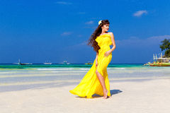 Beautiful brunette woman in a yellow dress on the tropical sea c Royalty Free Stock Photos