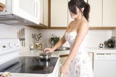 Beautiful brunette working in kitchen. Beautiful brunette housewife working in her kitchen Stock Photo