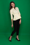 Beautiful brunette in a yellow blouse and black pants on a green royalty free stock photography