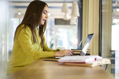 Beautiful brunette in a yellow blouse comments feedbacks moderating chats using laptop computer connected to wifi. Concentrated female content manager of popular stock photos