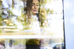 Beautiful brunette in a yellow blouse meeting and booking tickets for airplane while sitting in cafe. Pretty skilled female secretary assistant of successful Stock Photography