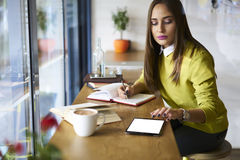 Beautiful brunette in a yellow blouse in online database checking accountings via touchpad with mock up screen connected to wifi. Young attractive female Royalty Free Stock Photos