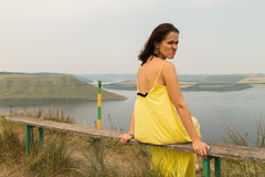 Beautiful brunette in a yellow dress on the riverbank. Nice view of the large pond. Stylish dress and makeup beautiful woman. Photos for magazines, posters and Stock Images