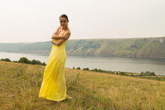 Beautiful brunette in a yellow dress on the riverbank. Nice view of the large pond. Stylish dress and makeup beautiful woman. Photos for magazines, posters and Stock Image