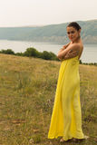 Beautiful brunette in a yellow dress on the riverbank. Nice view of the large pond. Stylish dress and makeup beautiful woman. Photos for magazines, posters and Royalty Free Stock Photo
