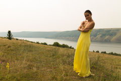 Beautiful brunette in a yellow dress on the riverbank. Nice view of the large pond. Stylish dress and makeup beautiful woman. Photos for magazines, posters and Stock Photos