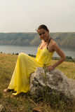 Beautiful brunette in a yellow dress on the riverbank. Nice view of the large pond. Stylish dress and makeup beautiful woman. Photos for magazines, posters and Stock Photography