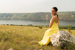 Beautiful brunette in a yellow dress on the riverbank. Nice view of the large pond. Stylish dress and makeup beautiful woman. Photos for magazines, posters and Royalty Free Stock Image