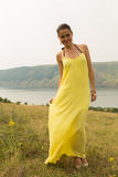 Beautiful brunette in a yellow dress on the riverbank Stock Images