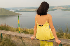 Beautiful brunette in a yellow dress on the riverbank Stock Photo