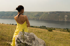 Beautiful brunette in a yellow dress on the riverbank Royalty Free Stock Photos