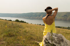 Beautiful brunette in a yellow dress on the riverbank Royalty Free Stock Photography