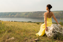 Beautiful brunette in a yellow dress on the riverbank Royalty Free Stock Image