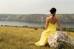 Beautiful brunette in a yellow dress on the riverbank Royalty Free Stock Photo