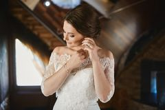 Beautiful brunette young bride in fashionable lace dress adjusting her earring and posing at rustic interior stock image