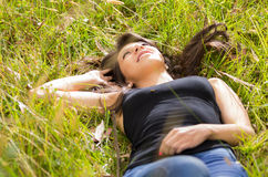 Beautiful brunette young girl resting on green Royalty Free Stock Photos