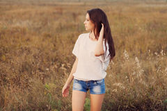 Beautiful brunette young lady at the autumn meadow. Stock Images