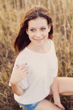 Beautiful brunette young lady at the autumn meadow smiling Royalty Free Stock Image