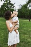 Beautiful brunette young mom in short white stylish dress holding on her hands and kissing her cute baby boy outdoors.  royalty free stock photo