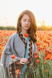 Romantic woman relaxing in poppy field at sunset. Beautiful brunette young woman with closed eyes relaxing in red poppy flower field at sunset in summer stock images