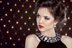 Beautiful brunette young woman. Fashion girl model over bokeh li. Ghts background Royalty Free Stock Image