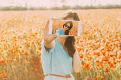 Woman taking selfie with smartphone in flowers field. Beautiful brunette young woman in glasses taking a photo selfie with smartphone in flowers meadow in stock photos