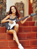 Beautiful brunette young woman with guitar sitting on stairs Stock Images