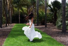 Beautiful brunette young woman dancing in nature with a long white dress royalty free stock photography