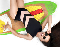 Beautiful brunette young woman lying on long surfboard board on. White background Royalty Free Stock Photos