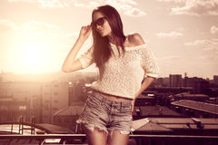 Beautiful brunette young woman posing above sunset city background Stock Images