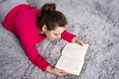 Beautiful brunette young woman is reading book on the bed in cozy apartment. Hobby reading books and fiction. Spending time with the book. A girl reads fiction Royalty Free Stock Images
